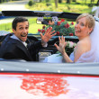 Young wedding couple waving in cabriolet car — Stock Photo