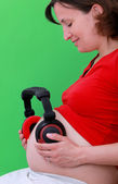 Pregnant woman with headphones on her stomach — 图库照片