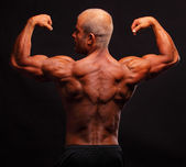 The muscular bodybuilder flexing biceps — Stock Photo