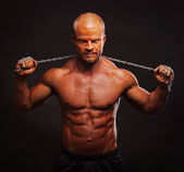 Muscular bodybuilder man with a chain — Stock Photo