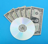 DVD disc with dollar notes — Stock Photo