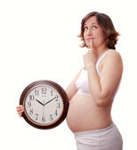 Young toughtfull pregnant woman with clock — Stock Photo