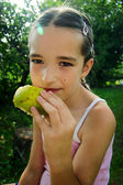 Young girl eating pear outdoor — Stock Photo