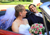 Young wedding couple sitting in cabriolet car — Stock Photo