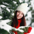 Young beautiful woman behind snow covered pine — Photo