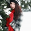 Young beautiful woman behind snow covered pine — Foto Stock