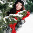 Young beautiful woman behind snow covered pine — Stockfoto
