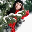 Young beautiful woman behind snow covered pine — Stok fotoğraf