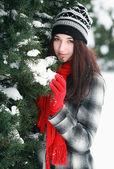 Hermosa joven detrás de nieve cubierto pino — Foto de Stock