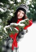 年轻漂亮的女人背后雪覆盖松 — 图库照片