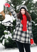 Young woman with ice skate in winter outdoor — Stock Photo