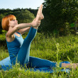 Red woman practicing fitness yoga outdoors — Stock Photo #15621417