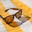 Stock Photo: Sunglasses on yellow beach towel