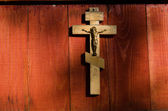 Small wooden crucifix hanging on wall — Stock Photo