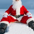 Santa sitting on sunbed in snow — Stockfoto