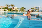 Young woman enjoying warm water in pool — Stock Photo