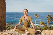 Young woman meditating near the sea — Stock Photo