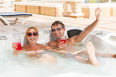 Young couple relaxing in jacuzzi pool — Stock Photo