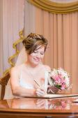 Belle mariée signe le certificat de mariage — Photo