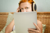 Red woman in bed listening to the music — Stock Photo