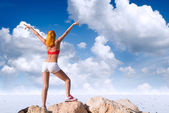 Fit young woman with raised hands above the desert — Stock Photo