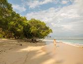 Young woman walking along tropical beach — Stock Photo