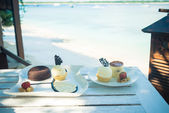 Delicious desserts at beach table — Stock Photo