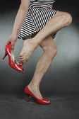 Woman putting on high heel shoes over grey background — Stock Photo