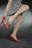 Femme mettant sur des chaussures à talons hauts sur fond gris — Photo