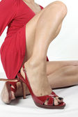 Woman putting on red heels — Stock Photo