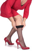 Woman in red dress putting on stockings — Stock Photo