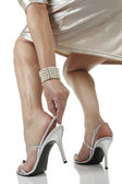 Woman wearing dress putting on silver heels — Photo