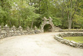 Stone archway and wall in a park setting — Stock Photo