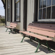 Two wooden benches by an old building — Stock Photo