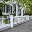 White picket fence by a typical federal style house — Stock Photo #34270241