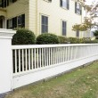 White picket fence by a typical federal style house — Stock Photo