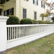 White picket fence by a typical federal style house — Stock Photo #34271883