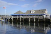 Shingle building by water and dock — Stock Photo