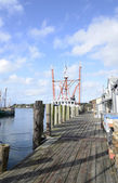Long wood dock by a commercial pier — Stock Photo