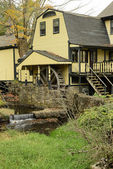 Yellow house with a waterwheel and waterfall — Stock Photo