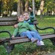 Boy and girl playing in the park bathed in autumn colors — Stock Photo