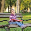Cute little girl is playing with leaves in autumn park — Stock Photo #32537751