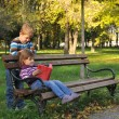 Cute little girl and boy is playing with leaves in autumn park — Stock Photo #32538875