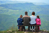 Family on a mountain lookout observing nature — Stockfoto