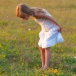 Cute little girl in white dress exploring meadow on sunny spring day — Stock Photo #12488366