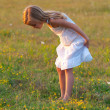 Cute little girl in white dress exploring the meadow on sunny spring day — Stock Photo
