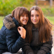 Two happy teenage girls having fun in the park on beautiful autumn day — Stock Photo