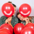 Cute teenage girls peeking behind smiling balloons — Stock Photo #12603200