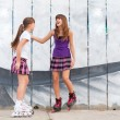 Two cute teenage girls on roller skates having fun in urban environment - Stock Photo