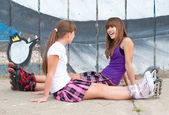 Two happy teenage girls in roller skates and short skirts having fun in urban environment — Stock Photo
